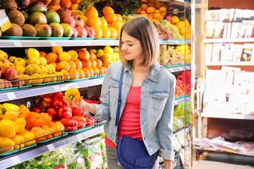 Beautiful woman choosing fresh bell pepper in supermarket