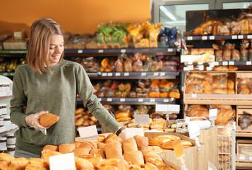 Beautiful woman choosing fresh bakery in supermarket