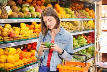Beautiful woman choosing fresh avocado in supermarket