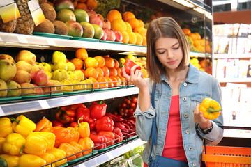 Beautiful woman choosing fresh bell peppers in supermarket