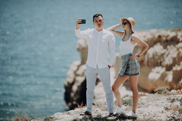 Young couple taking selfie self portrait photo on the top of cliff on ocean background. Happy lovers, woman and man traveling on vacation