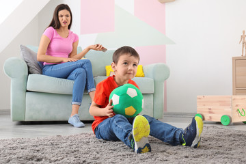 Little boy with ball and annoyed nanny in room