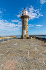 Whitby Lighthouse against blue sky - North Yorkshire, England