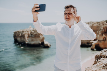 Handsome man taking a selfie on vacation with victory sign on ocean background