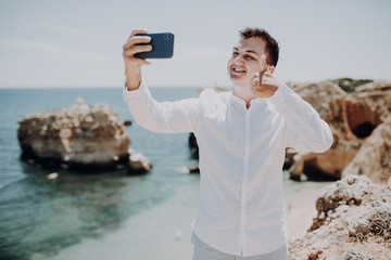 Handsome business man taking a selfie or make video call with thumbs up on vacation