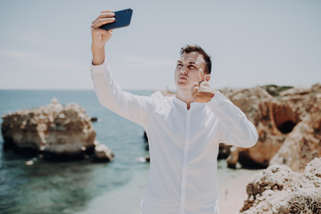 Handsome man taking a selfie with thumbs up at cliff ocean beach