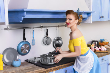 Colorful retro / pin up girl woman female / housewife wearing colorful top, skirt and white apron holding ladle and cooking soup in the kitchen with blue cabinets and utensils. Housework concept