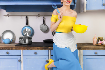 Colorful retro / pin up girl woman female / housewife wearing colorful top, skirt and white apron holding whipper and bowl making sweet cake in the kitchen with blue cabinets and utensils. Housework