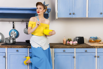 Colorful retro / pin up girl woman female  / housewife wearing colorful top, skirt and white apron holding whipper and bowl in the kitchen with blue cabinets and utensils and cupcakes with milkshake.