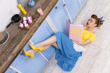 Colorful retro / pin up girl / housewife wearing colorful top, skirt and white apron lying on the floor in the kitchen and reading pink book. Sweet food cupcakes and milkshake home cooked on the table