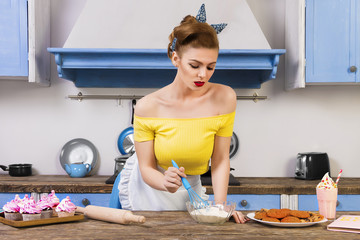 Coloful retro / pin up girl woman female / housewife wearing colorful top, skirt and white apron cooking in the kitchen with home backed cookies, cupcakes and milkshake standing on the table
