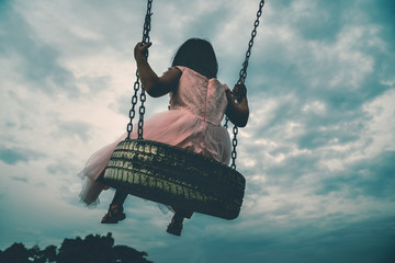 Little girl with skirt play swing at outdoor park. Dramatic sky