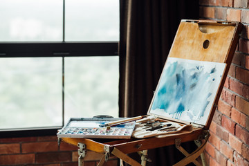 painting art hobby. creative leisure. drawing instruments and tools. artist watercolors brushes and easel with an abstract picture.