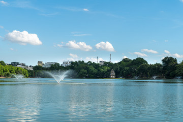 Hoan Kiem lake or Sword lake, Ho Guom in Hanoi, Vietnam with Turtle Tower, on clear day with blue sky and white clouds