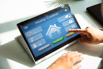 Person using home control system on laptop