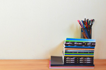 School supplies including stack of colorful  notebooks pencil holder with scissors pens and brushes on wooden table on light yellow wall background with copy space for text. Back to school concept.
