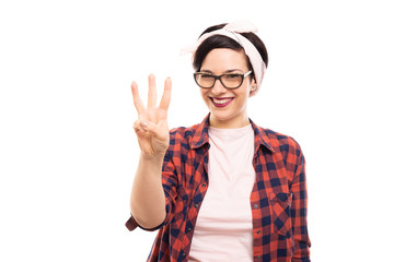 Pretty pin-up girl wearing glasses showing number three with fingers.