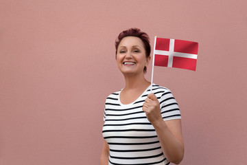 Denmark flag. Woman holding Danish flag. Nice portrait of middle aged lady 40 50 years old with a national flag over pink wall background.Learn Danish language. Visit Denmark concept.