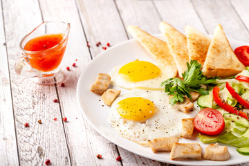 English cuisine, breakfast on a white plate of fried eggs, vegetables and salad with chicken, fried bread toast. Copy space, selective focus