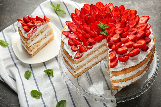 Stand and plate with delicious strawberry cake on table