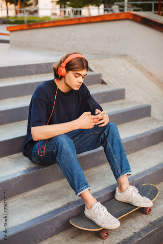Young skater in orange headphones thoughtfully using