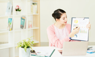 happy young woman working on laptop in workplace.entrepreneur working at start up.Business woman in office start-up working on laptop.