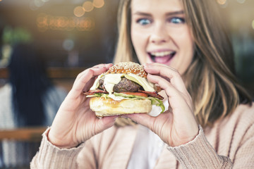 Excited young woman lifts giant burger to her mouth
