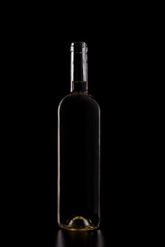 Silhouette of white wine bottle isolated on black dark background with soft reflections and beautiful shadows. Studio shot.