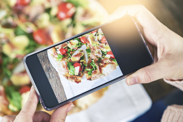 Hands using phone to photograph pizza at restaurant