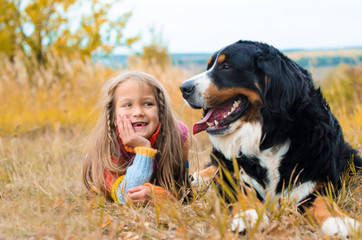girl lies next to big dog on autumn walk Berner Sennenhund Papier Peint