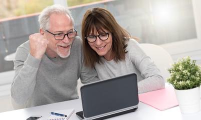 Happy mature couple having a good surprise on laptop