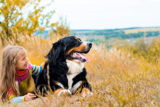 girl lies next to big dog on autumn walk Berner Sennenhund