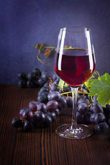 Still life of glass with red wine and grapes