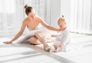 Little girl is taught how to tie ballet pointe shoes