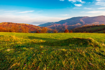 grassy meadow on hill side at sunrise in autumn. beautiful mountainous landscape with distant valley in fog