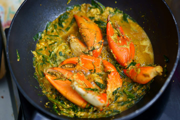 Crab in curry fried in pan in kitchen