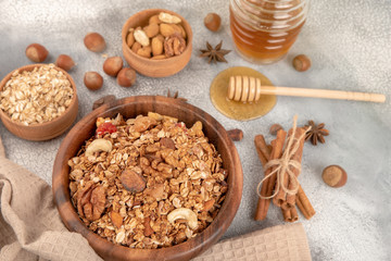 Homemade granola in wooden bowl with ingredients - oat, nuts, honey and spice cinnamon and anise