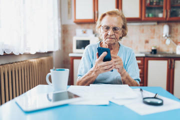 Elderly woman contacting custumer services after recieving a bill