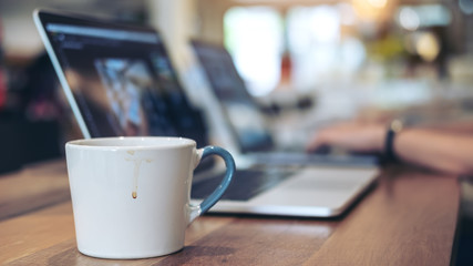 Closeup image of people working and typing on laptop keyboard with coffee cup on table in office