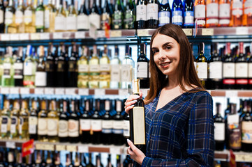 Shopping woman looking at the shelves in the supermarket.  Portrait of a young girl in a market store at alcohol sector with bottle of wine at hands.