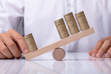 Businessperson Showing Unbalance Between Stacked Coins