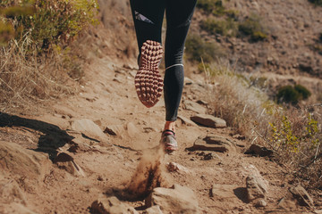 Woman runner running on mountain trail