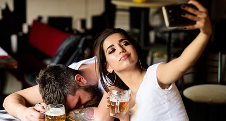 Take selfie to remember great event. Woman making fun of drunk friend. Man drunk fall asleep table and girl with full beer glass. Girl taking selfie photo drunk boyfriend. He appears too weak for her