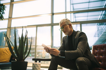 Senior executive texting on cell phone in office lobby