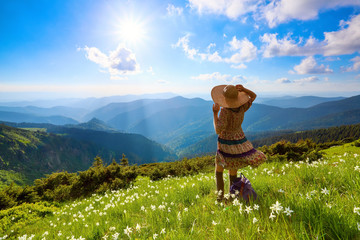 On the lawn in mountains landscapes the hipster girl in dress. The rays of the sun poke through the white clouds.