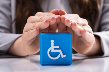 Woman Protecting Cubic Block With Disabled Handicap Icon