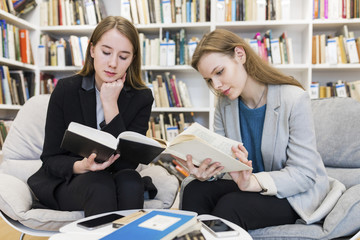 Two teenage girls sitting in a public library reading books
