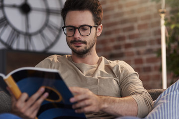 Portrait of man sitting on couch at home reading a book