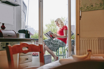 Pregnant woman sitting on balcony looking at photo book
