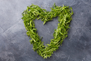 Green leaves of arugula laid out in the shape of heart on dark background.